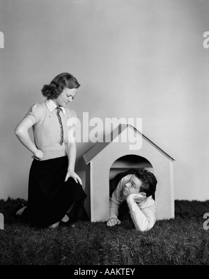 1940s YOUNG TEEN COUPLE ARGUMENT GIRL FROWNING BOY LYING IN DOGHOUSE DOG HOUSE - Stock Photo