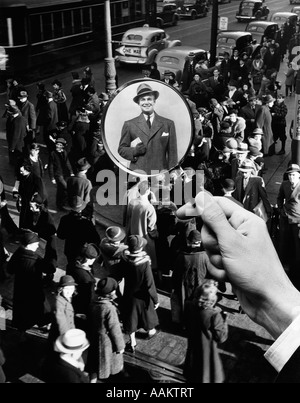 1930s 1940s PEDESTRIAN STREET CROWD MAGNIFYING GLASS FOCUSED ON SINGLE WELL DRESSED MAN A FACE IN THE CROWD - Stock Photo