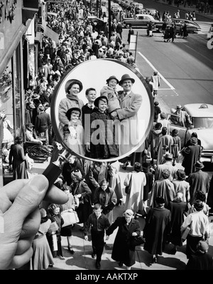 1950s MONTAGE OF FAMILY IN MAGNIFYING GLASS SUPERIMPOSED OVER CROWDED SIDEWALK - Stock Photo