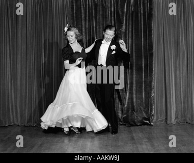 1940s COUPLE MAN AND WOMAN IN FORMAL WEAR BALLROOM DANCING ON STAGE - Stock Photo