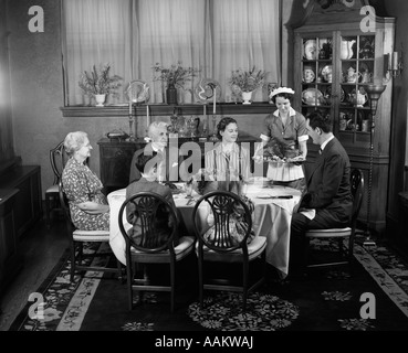 1940s TWO GENERATION FAMILY IN DINING ROOM THANKSGIVING TURKEY BEING SERVED BY MAID - Stock Photo