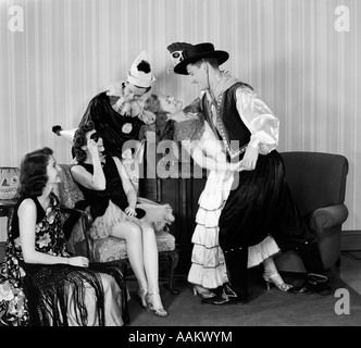 1930s 1940s YOUNG COUPLES DRESSED IN COSTUMES DANCING AT HOME HALLOWEEN PARTY - Stock Photo