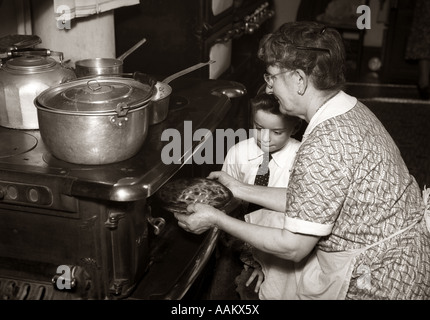 1930s 1940s BOY WATCHING GRANDMOTHER TAKING PIE OUT OF CAST IRON WOOD BURNING STOVE OVEN - Stock Photo