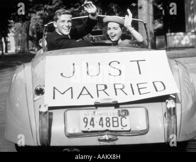1950s NEWLYWED YOUNG COUPLE MAN WOMAN IN CONVERTIBLE SPORTS CAR WITH JUST MARRIED SIGN WAVING LOOKING