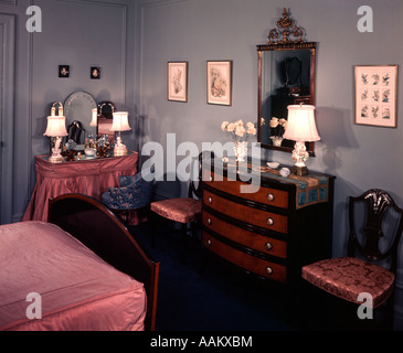 1930s 1940s BEDROOM WITH BLUE WALLS PINK BEDSPREAD AND SKIRTED VANITY TABLE - Stock Photo