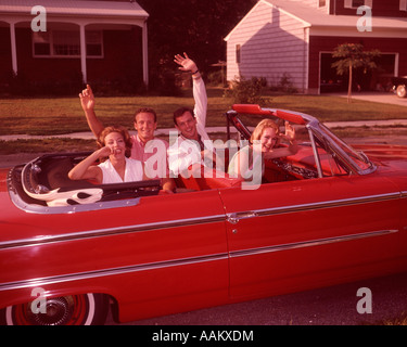 1960s TWO YOUNG COUPLES IN RED CONVERTIBLE AUTOMOBILE ON SUBURBAN STREET LAUGHING WAVING HANDS LOOKING AT CAMERA - Stock Photo