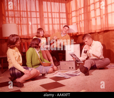 1960s GROUP OF TEENS PLAYING RECORDS ON PORTABLE PHONOGRAPH DRINKING SODAS - Stock Photo
