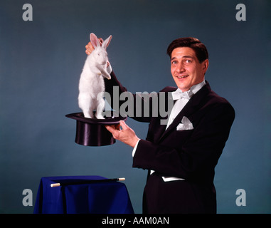 1960s 1970s MAN MAGICIAN TUXEDO PULLING RABBIT OUT OF TOP HAT MAGIC ILLUSION SLEIGHT OF HAND TRICK - Stock Photo