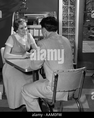 1950s TEEN COUPLE SITS AT TABLE IN DINER JUKEBOX IN BACKGROUND SMILING INDOOR - Stock Photo