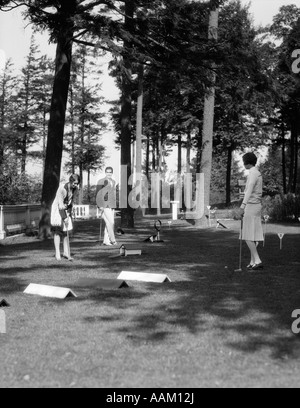 1920s 1930s MAN TWO WOMEN PLAYING MINIATURE OBSTACLE GOLF COURSE - Stock Photo