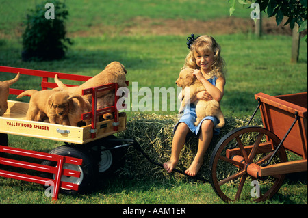 1990s SMILING LITTLE BAREFOOT BLONDE FARM GIRL PLAYING WITH SEVERAL PUPPIES LOOKING AT CAMERA - Stock Photo