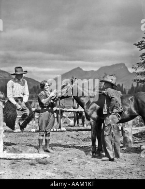 1930s TWO COWBOYS & A WOMAN GROOMING A HORSE NEAR THE CORRAL THE STANDING COWBOY IS WEARING BATWING CHAPS - Stock Photo