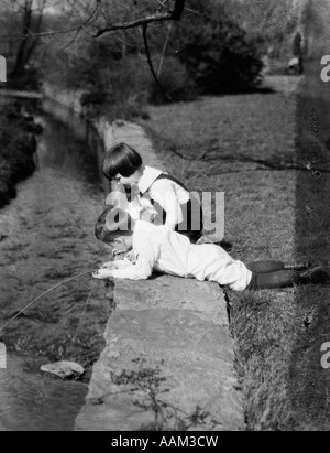 1920s TWO BOYS PLAYING IN WATER STREAM CREEK BOY LYING GROUND STRING FISHING ANGLING SUMMER FUN PLAY - Stock Photo