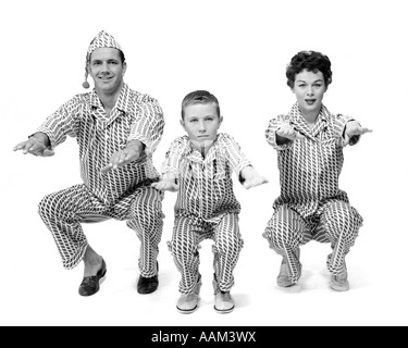 1950s FAMILY OF 3 IN PAJAMAS DOING KNEE BENDS FACING CAMERA - Stock Photo