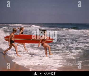 1970s ONE TEENAGE BOY TWO GIRLS IN BATHING SUITS LAUGHING RUNNING INTO OCEAN SURF CARRYING A RED SURFBOARD - Stock Photo