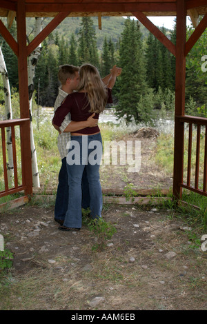 Vertical   Young couple dancing in a gazebo, playing and having a good time. - Stock Photo