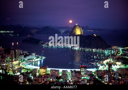 Sugar Loaf Mountain and Botafogo inlet Rio de Janeiro skyline at night with moon Brazil - Stock Photo