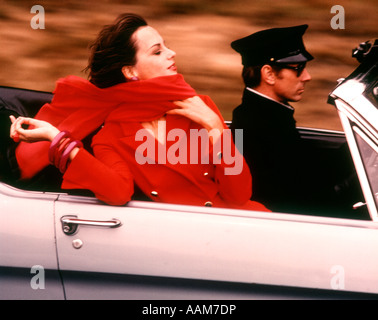 1970 1970s STYLISH WOMAN RED DRESS SCARF DRIVING OPEN AIR CONVERTIBLE SPORTS CAR CHAUFFEUR STYLE FASHION WEALTH - Stock Photo