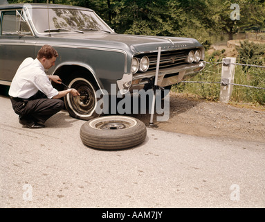 1960s MAN CHANGING FLAT TIRE ON CAR AT SIDE OF RURAL ROAD CAR JACK TOOLS TIRE IRON - Stock Photo