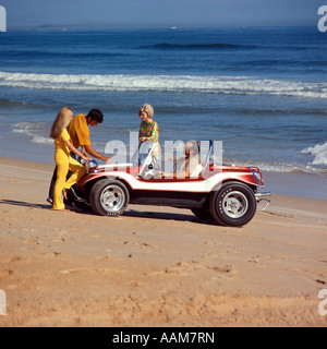 1970 1970s 2 COUPLES MEN WOMEN ON BEACH WITH RED WHITE DUNE BUGGY LEISURE SPORT LIFESTYLE VEHICLE FUN SUMMER - Stock Photo