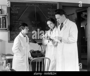 1930s 1940s THREE SCIENTISTS IN WHITE LAB COATS CONSULTING BOOK ONE MAN TWO WOMEN BLACKBOARD - Stock Photo