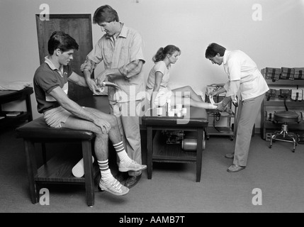 1980s MEDICAL OFFICE TEEN BOY HAVING WRIST BANDAGED & TEEN GIRL HAVING ANKLE BANDAGED - Stock Photo