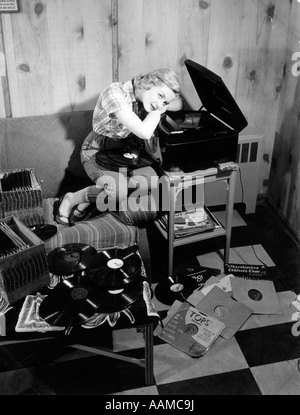 1950s TEEN GIRL LISTENING TO MUSIC ON PHONOGRAPH SIT ON COUCH LEAN ON RECORD PLAYER DREAMING RECORDS 78s - Stock Photo