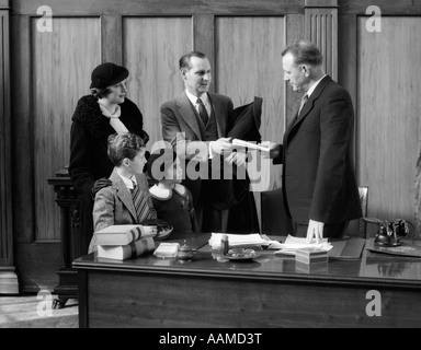 1930s FAMILY IN OFFICE TALKING WITH EMPLOYEE - Stock Photo