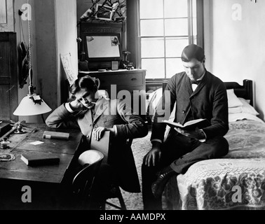 1890s 1894 PAIR OF MALE STUDENTS STUDYING IN DORM ROOM - Stock Photo