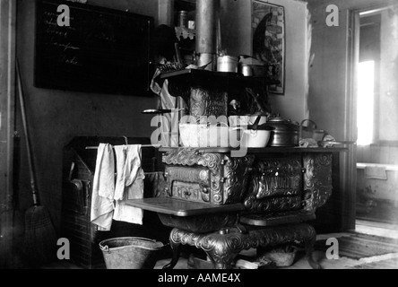 1890s 1900s TURN OF CENTURY CAST IRON WOOD BURNING COOK STOVE WITH POTS AND PANS IN KITCHEN - Stock Photo