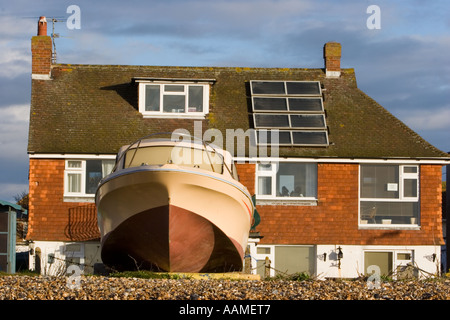 Holiday homes with roof mounted solar panels overlooking the beach in East Sussex UK - Stock Photo