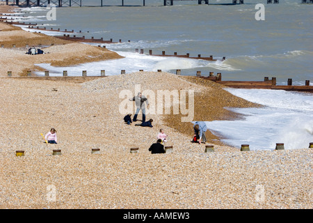 The beach at Eastbourne as seen from the pier with men throwing stones into the sea - Stock Photo