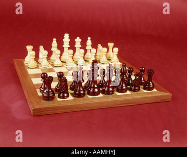 1970s CHESS SET ARRANGED ON BOARD STILL LIFE RED AND WHITE CHESS PIECES GAME 1970s - Stock Photo