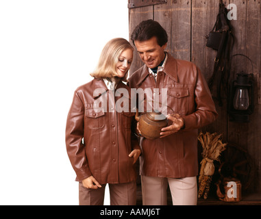 1970 1970s COUPLE WEARING MATCHED MATCHING LEATHER JACKETS HOLDING ANTIQUE COPPER TEA KETTLE RETRO - Stock Photo
