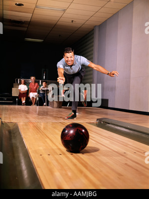 1960s SMILING MAN IN GOOD FORM RELEASING BOWLING BALL DOWN LANE WIFE WOMAN 2 KIDS LOOK ON RECREATION FAMILY FUN - Stock Photo