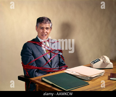 1970s MIDDLE AGED BUSINESS MAN AT DESK TIED UP TANGLED IN RED TAPE OFFICE SNAFU BUREAUCRACY WASTEFUL RETRO VINTAGE - Stock Photo