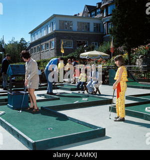 1960s FAMILY PLAYING GAME OF MINIATURE GOLF MOM DAD 3 KIDS SUMMER VACATION FUN GREEN PUTT - Stock Photo