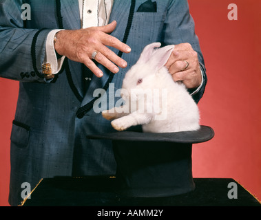 MAN MAGICIAN PULLING RABBIT OUT OF HAT - Stock Photo