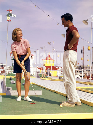 1960s YOUNG COUPLE PLUING MINIATURE GOLF - Stock Photo