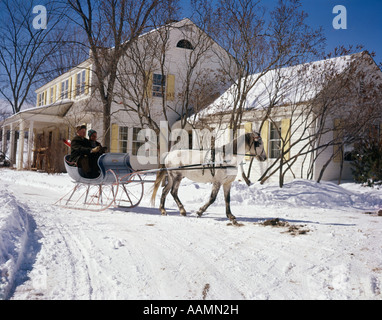1960s 2 MEN IN ONE WHITE HORSE DRAWN OPEN SLEIGH BY COUNTRY HOUSE INN SNOW RETRO VINTAGE WINTER VERMONT - Stock Photo