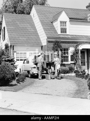 1950s FAMILY MOTHER FATHER SON IN FRONT OF SUBURBAN HOUSE LOADING CAR TRUNK WITH LUGGAGE SUITCASE GOLF BAG TRIP - Stock Photo