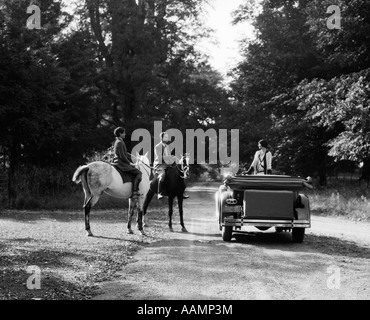 1920s 1930s COUPLE ON HORSES MEETING WOMAN ON ROAD IN CONVERTIBLE TOURING CAR - Stock Photo