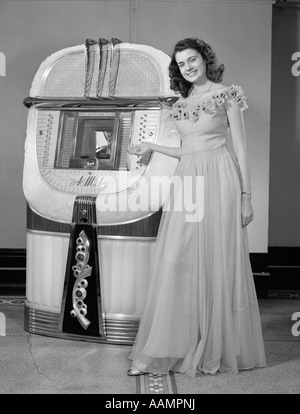 1940s PORTRAIT OF WOMAN IN BALL GOWN IN FRONT OF JUKEBOX - Stock Photo