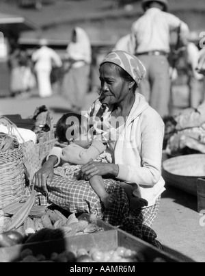 1920s 1930s MOTHER SITTING HOLDING BABY CHILD NURSING IN MARKET PLACE WOMAN SMOKING CIGAR CHEROOT BAGUIO PHILIPPINES - Stock Photo