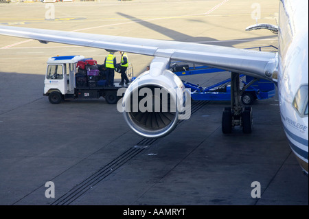 baggage handlers and baggage vehicle behind wing of privilege hola airlines boeing 757 256 plane sitting on stand - Stock Photo