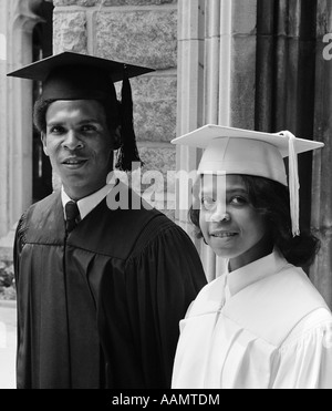 1970s PORTRAIT AFRICAN AMERICAN COUPLE MAN WOMAN WEARING GRADUATION GOWNS TOGETHER LOOKING AT CAMERA - Stock Photo