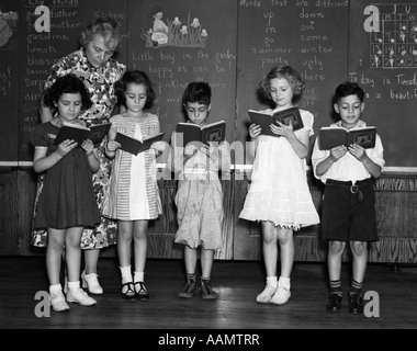 1930s LINE-UP OF 5 ELEMENTARY SCHOOL STUDENTS IN FRONT OF BLACKBOARD READING BOOKS WITH TEACHER LOOKING ON - Stock Photo