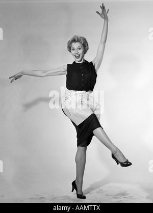 1950s BLONDE WOMAN IN APRON HOUSEWIFE DANCING KICKING HER LEG LOOKING AT CAMERA - Stock Photo
