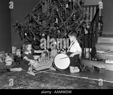 1930s 1940s BOY AND GIRL PLAYING WITH TOYS AND PRESENTS BY CHRISTMAS TREE - Stock Photo
