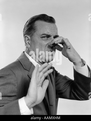 1950s 1960s MAN 3/4 PROFILE HAND HOLDING NOSE CLOSED HAND OUT TOWARD CAMERA FACIAL EXPRESSION DISGUST STINKING - Stock Photo